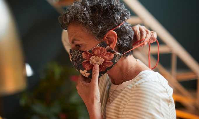 woman adjusts cloth face mask to make it more comfortable 682x408