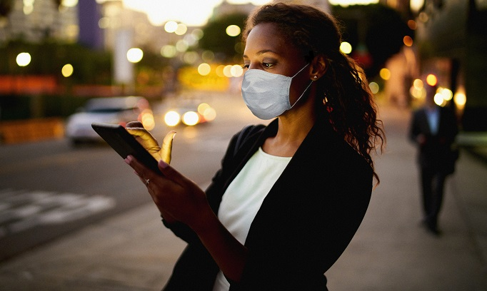 Black woman wearing a face mask checks her cell phone outdoors in city at dusk 682x408