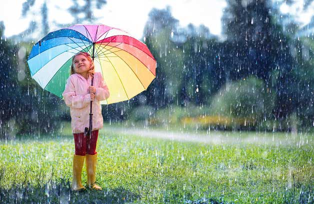 girl with rainbow umbrella in light rain during coronavirus quarantine