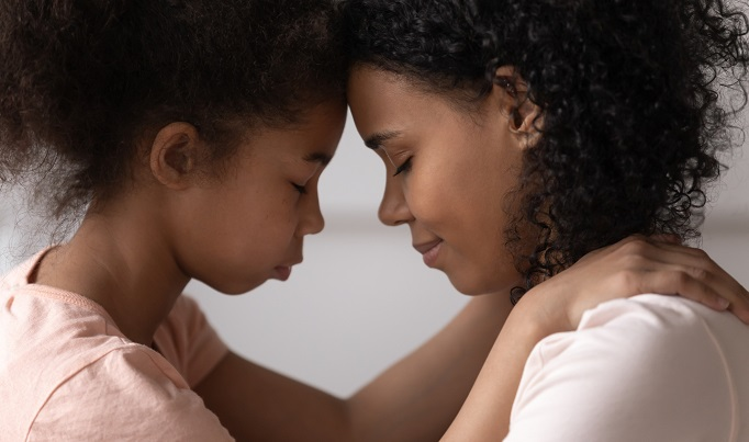 an african american mother and daughter touch foreheads while talking