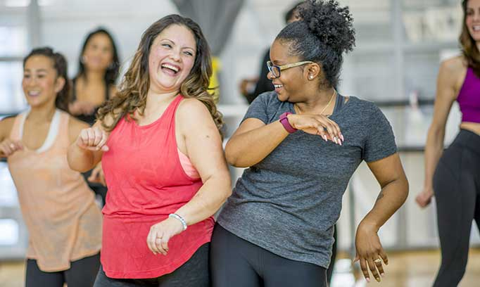 Group of women of every size dancing in an exercise class.