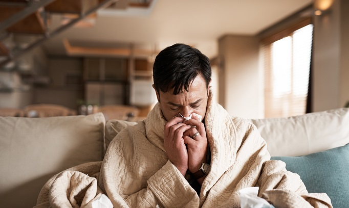 man on sofa sneezing tissues cold flu
