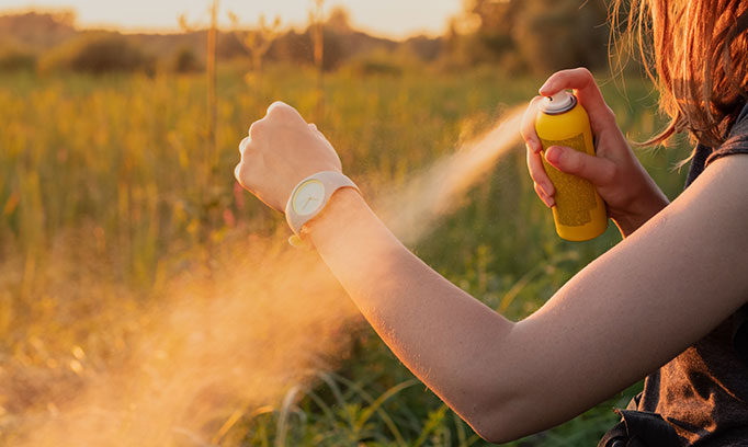 woman sprays insect repellent to prevent bug bites