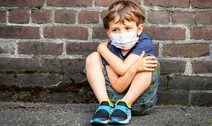 Young brown haired boy in blue shirt, shorts and sneakers and wearing a white face cover sits huddled on ground with his back against a brick wall. His knees are up to his chest and his arms around around his knees. He looks anxious.kids back to school anxiety