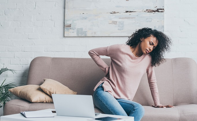 woman with lower back pain sitting on couch