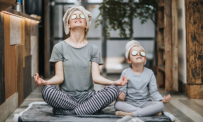 mom and daughter in yoga pose with cucumber slices over their eyes
