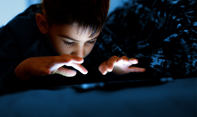 boy looking at an electronic device in the dark